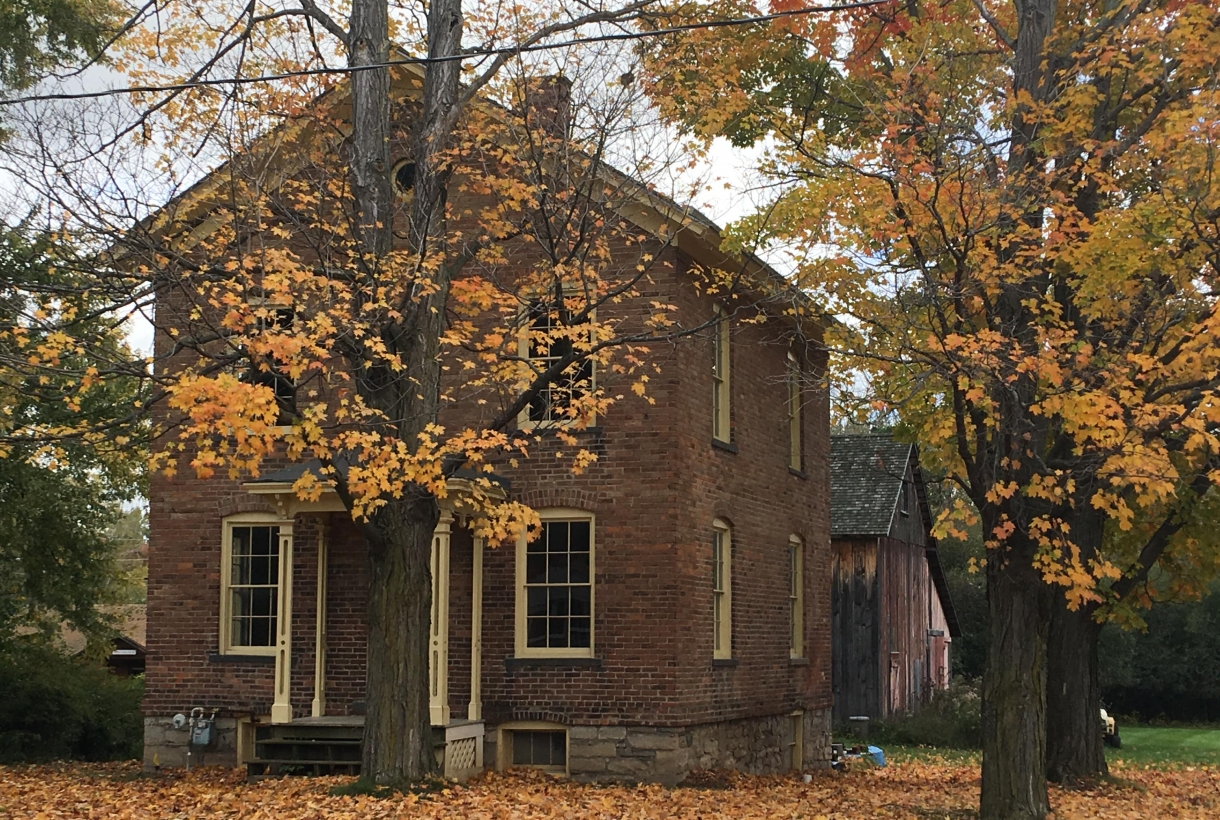 Brick building of Harriet Tubman residence surrounded by the yellow leaves of fall foliage at Harriet Tubman National Historical Monument
