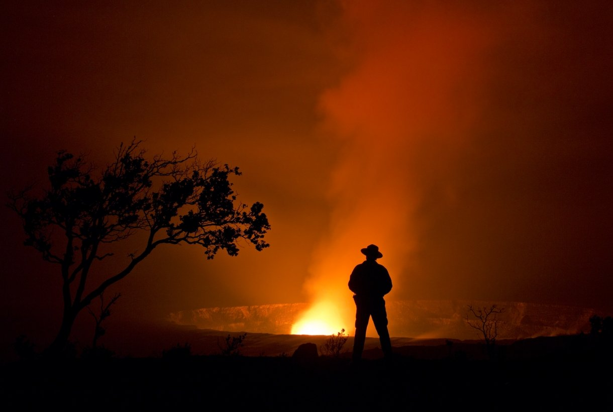 A ranger stands before the glow of Halema'uma'u crater on Kilauea Volcano in Hawai'i Volcanoes National Park.