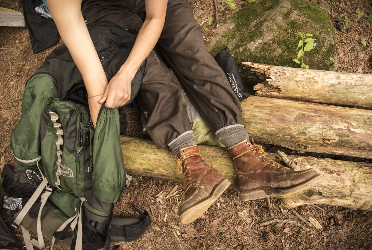 Someone sits on a log next to a backpack. Their legs stretch out. They wear hiking boots and pants.