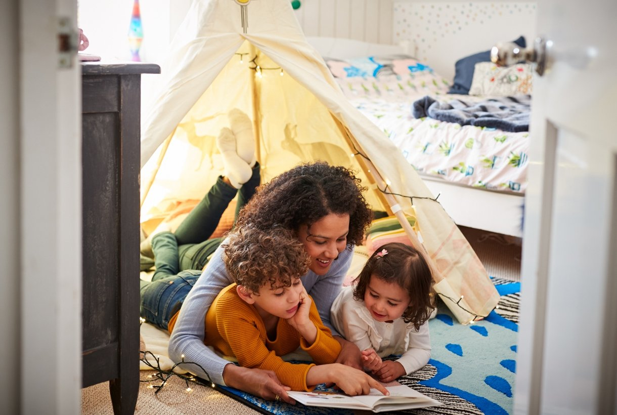 A woman and two young children lay in a small tent, set up indoors, and read a book on the floor