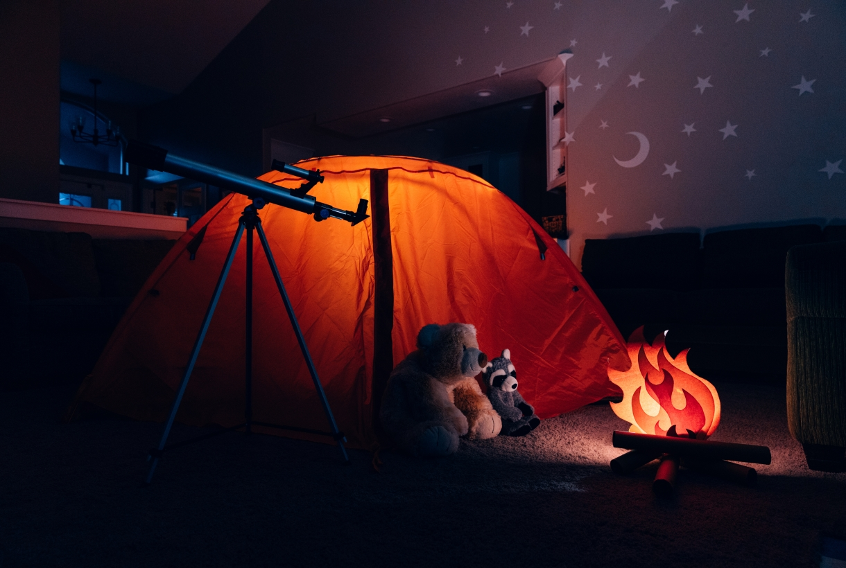 "A campsite set up indoors, with a paper ""campfire,"" surrounded by stuffed animals (bear, raccoon), and an illuminated red tent. A small telescope points away toward the sky in the distance. Stars are projected on the walls."