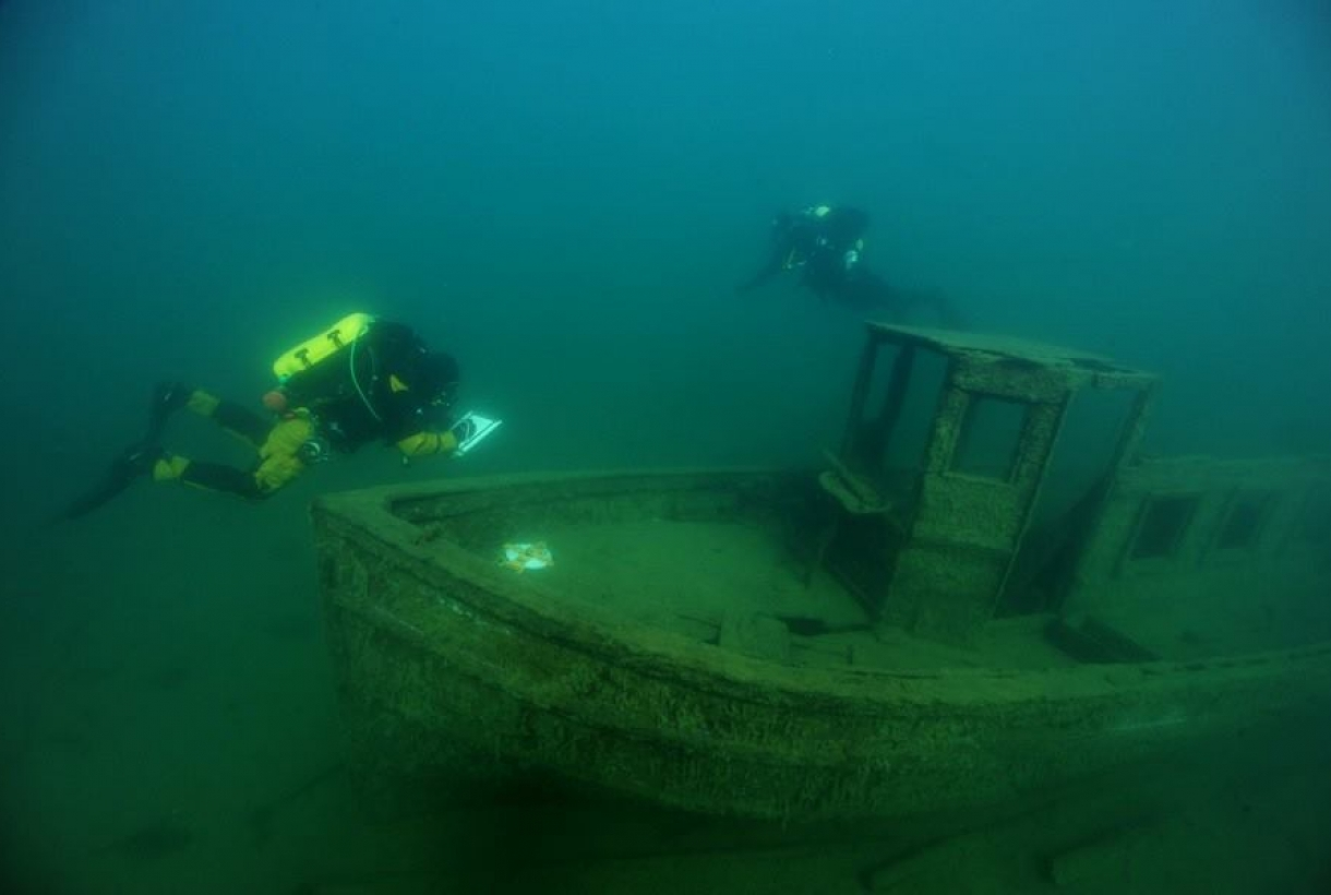 Two SCUBA divers looking at an underwater shipwreck at Isle Royal National Park