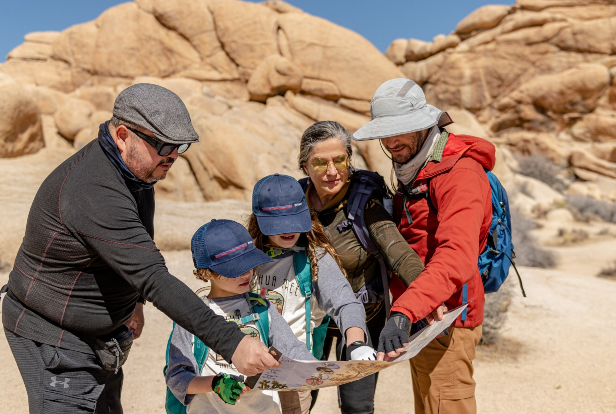 visitors using a map surrounded by large boulders