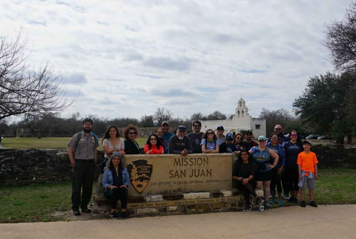 "A group standing outside next to a ""Mission San Juan"" sign"