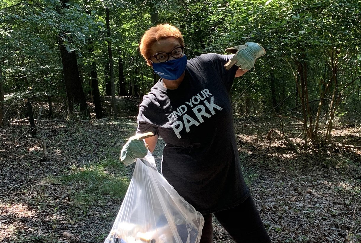 "LaTresse Snead points at her ""Find Your Park"" tshirt while she does some park cleanup work"
