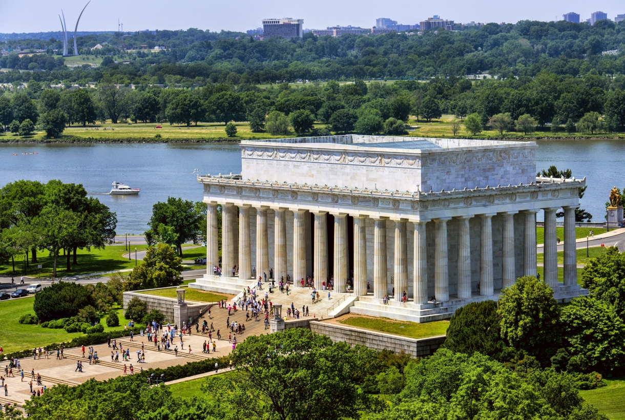 An aerial view of the marble Lincoln Memorial. Several visitors walk up its stairs