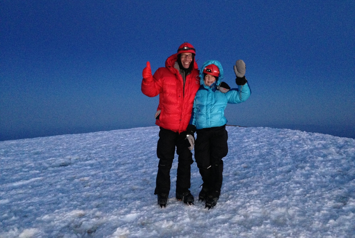 Lucy and her dad standing on completely snow-covered ground at Mount Rainier, giving the thumbs up