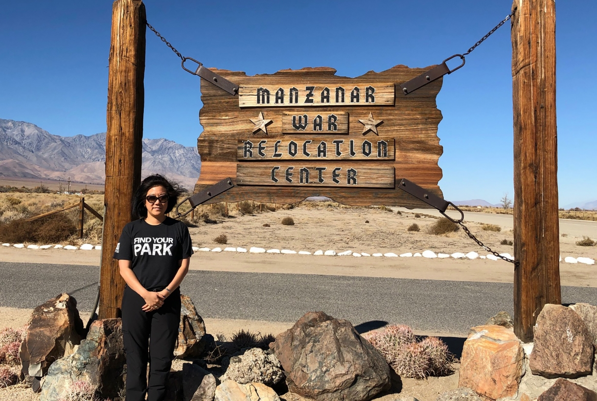 Kim Hirose Tobe stands in front of the sign at Manzanar National Historic Site