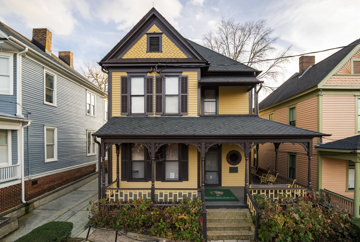 A yellow two-story home with green and brown trim. A handful of steps lead to a covered porch.