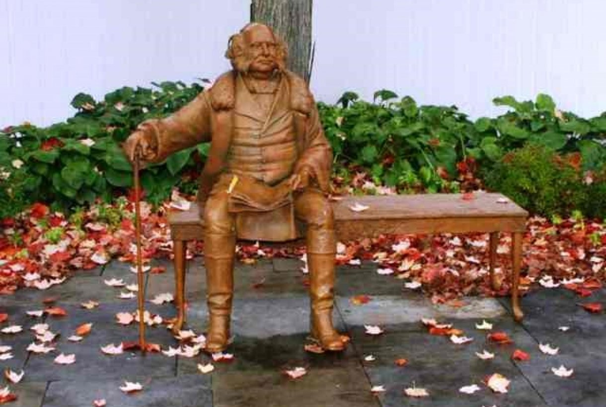 Martin Van Buren statue sits on a bench, with autumn, colorful leaves gathered at his feet