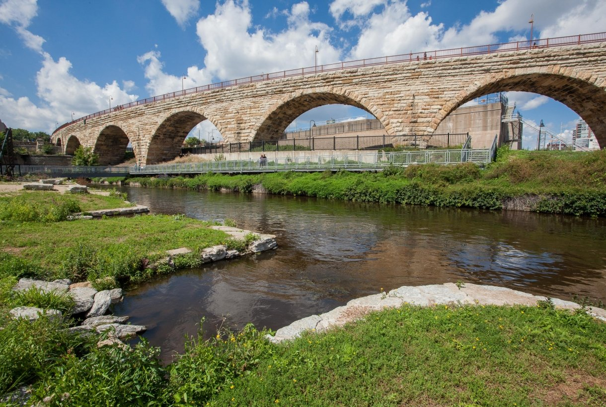 A bridge build from local stone, with its multiple arches, spans a river