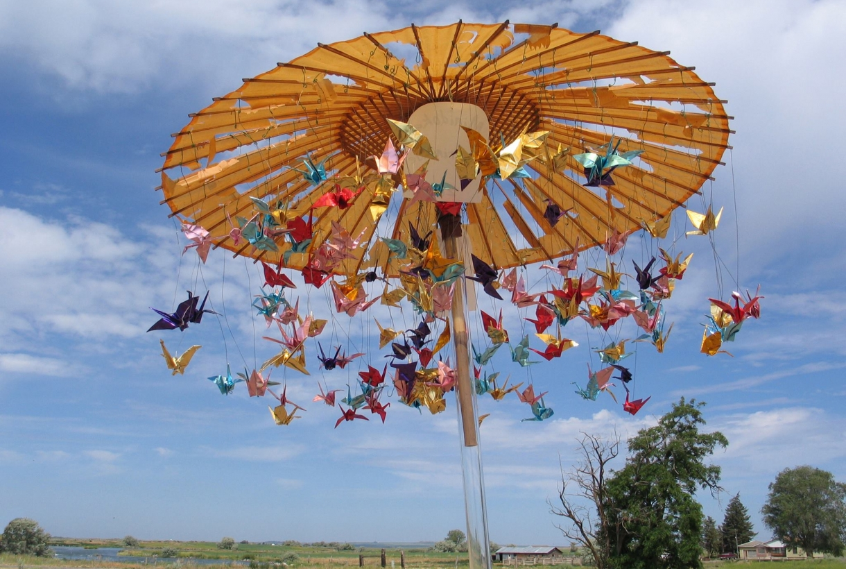 Colorful paper cranes hanging off of a Japanese umbrella under blue skies at Minidoka National Historic Site