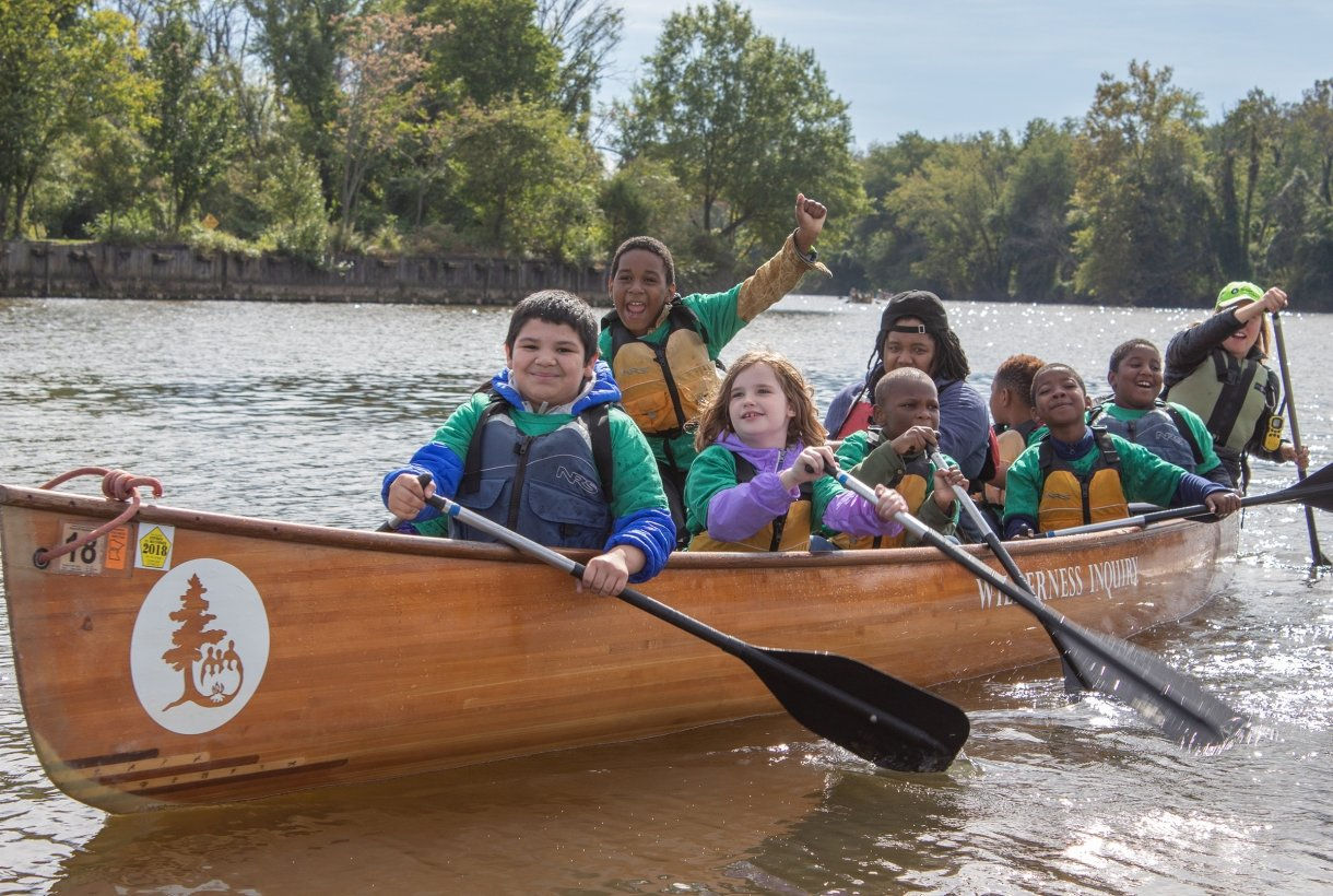 A group of youth, wearing lifejackets, canoe on a river