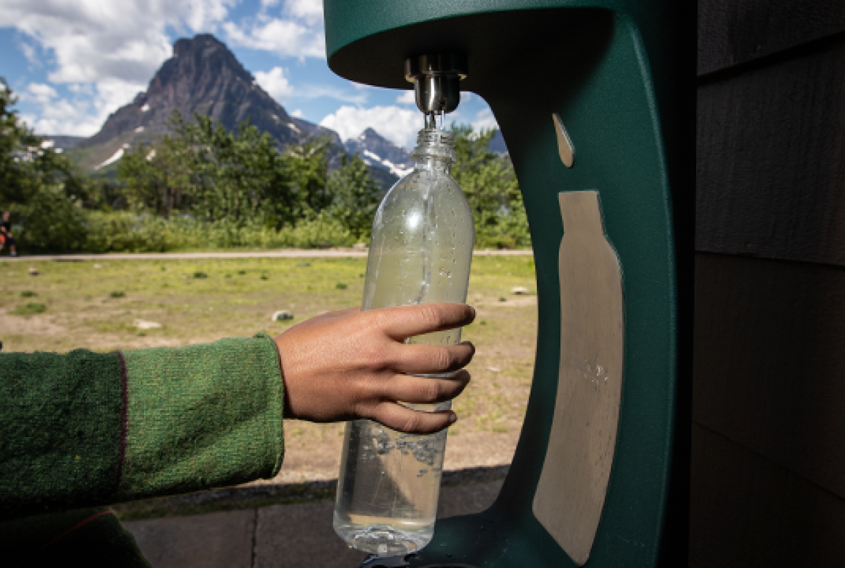 A hand reaches out to refill a waterbottle at a bottle refill station in a park
