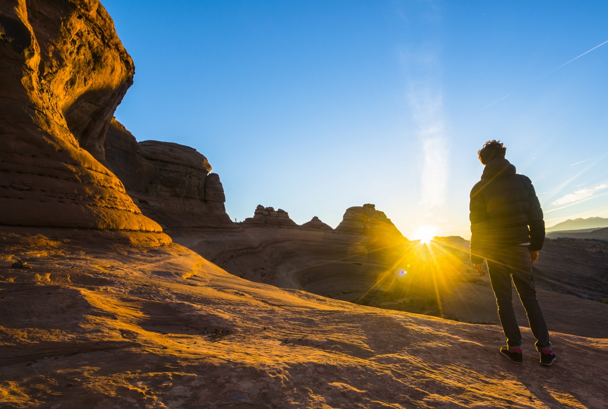Man standing facing setting sun at Arches National Park