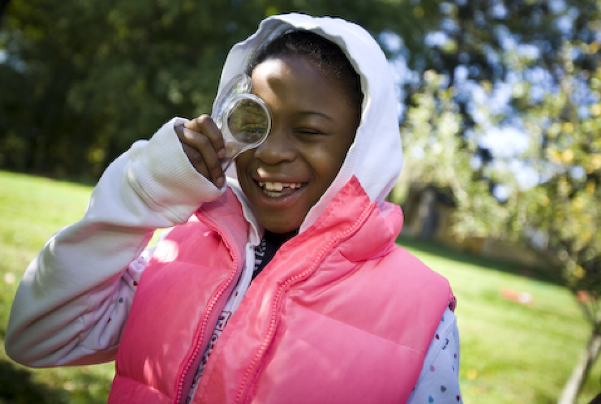 Image of African American girl smiling and looking through magnifying glass