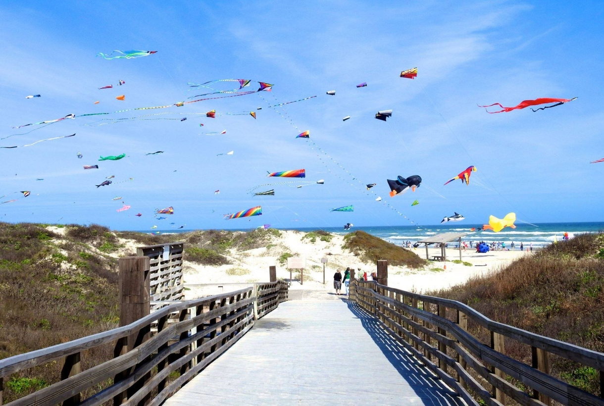 Myriad of colorful kites flying over the sandy beach of Padre Island National Seashore