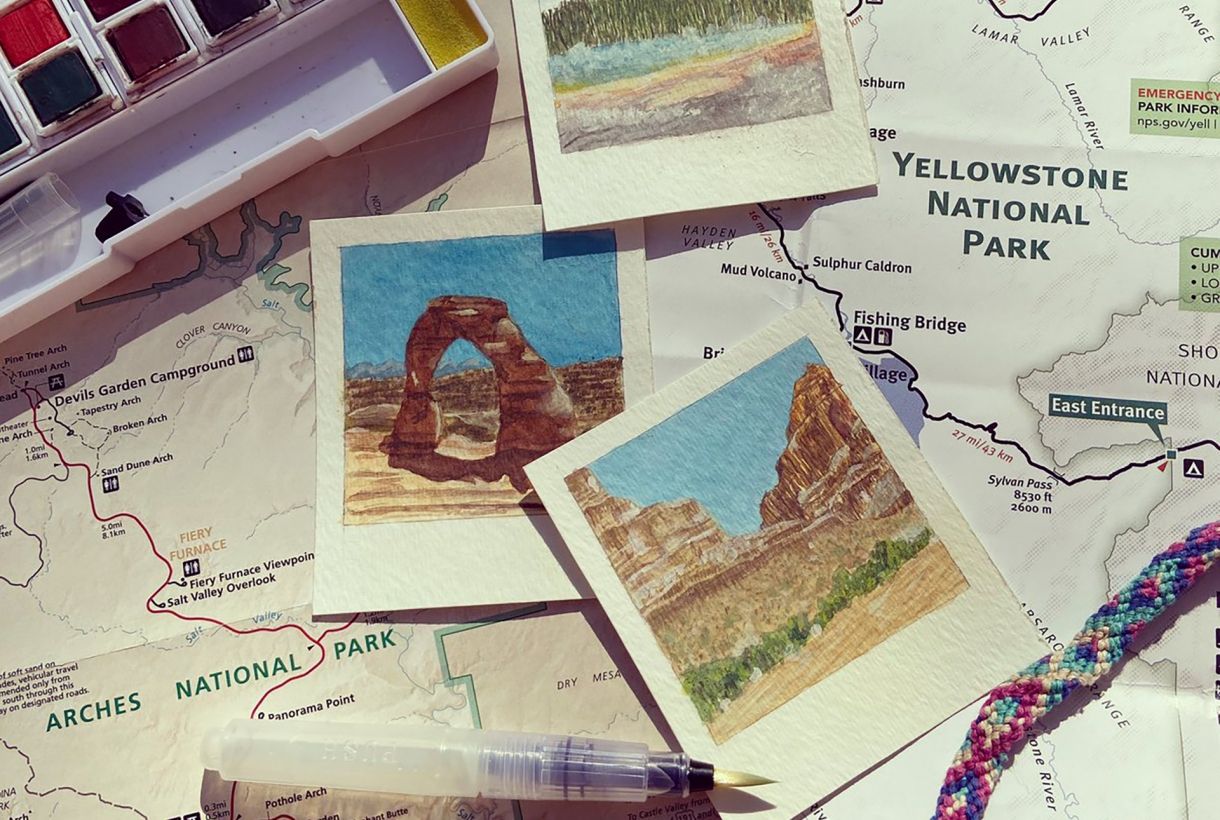 Atop a map of Yellowstone National Park, a set of watercolor paints, a watercolor paint pen, three small pictures of parks (painted in watercolor) and a braided bracelet