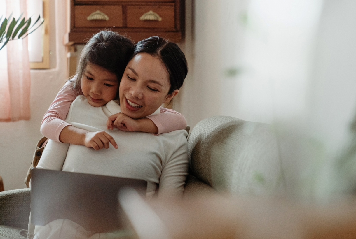 Mother and daughter doing online activities at home