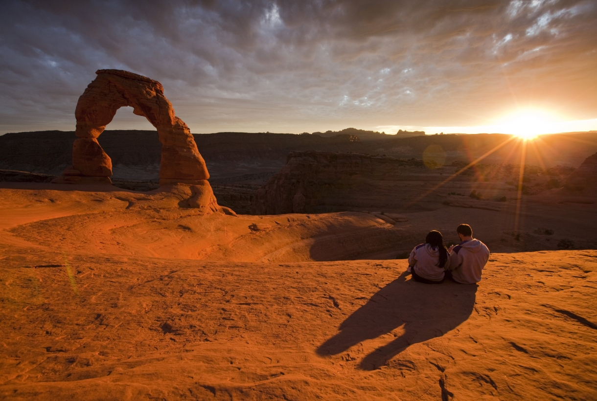 A couple sitting on on the sandstone cliffs with an arch to the left as the sun is setting behind the cliffs