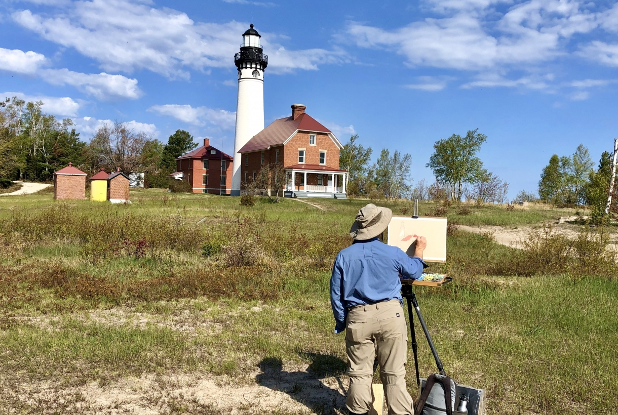 Artist drawing on a easel. He is looking at the keepers quarters and lighthouse in the distance.