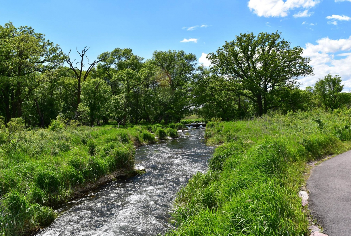 Pipestone Creek surrounded by lush green plants on the banks of the river at Pipestone National Monument