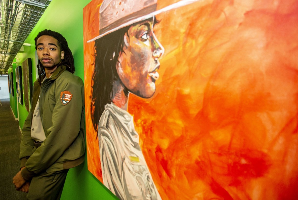 National Park Service Guide Elijah Prince stands against a bright green wall with one of his paintings