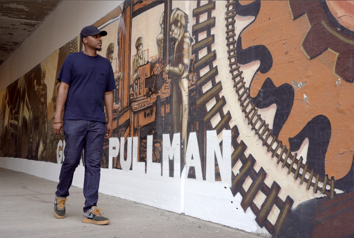 Artist Joe Nelson walks by a painted mural depicting the story of Pullman National Monument