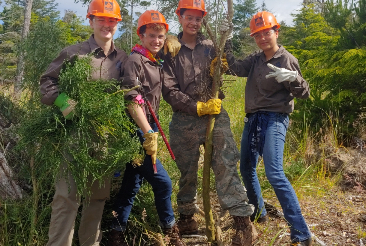 Four service corps members, in orange hard hats, pose with cleared greenery on a trail