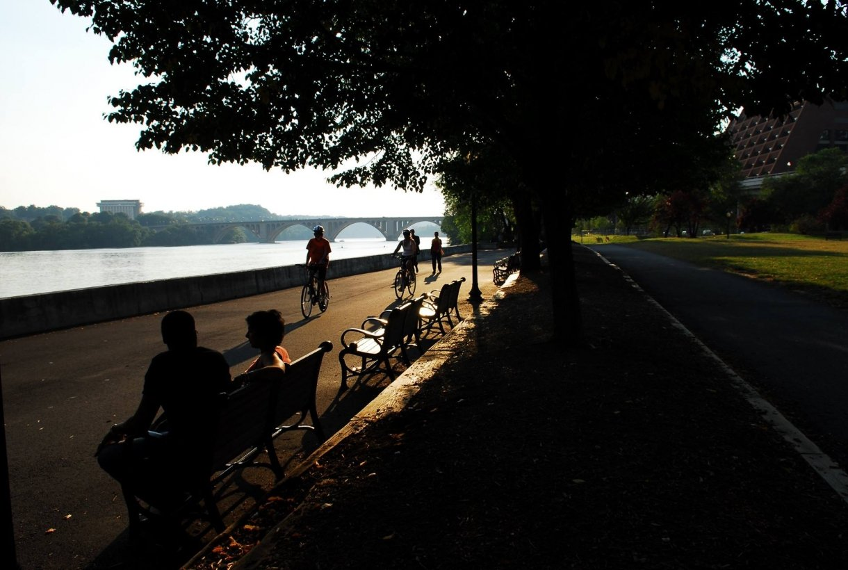A couple sitting on a park bench and bikers on a paved pathway next to the Potomac River along the Georgetown Waterfront Park in Rock Creek Park in Washington, DC