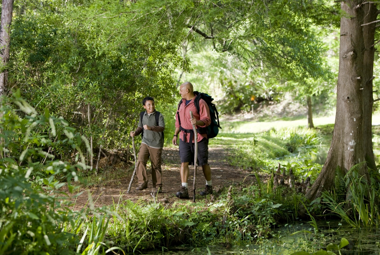 Man hiking with his son through the woods