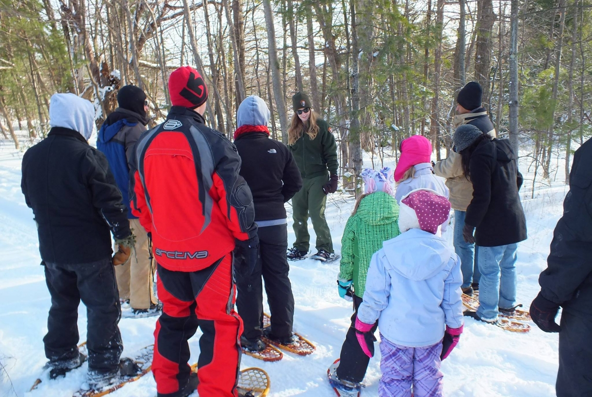 A group of people led by a park ranger snowshoeing at Sleeping Bear Dunes National Lakeshore