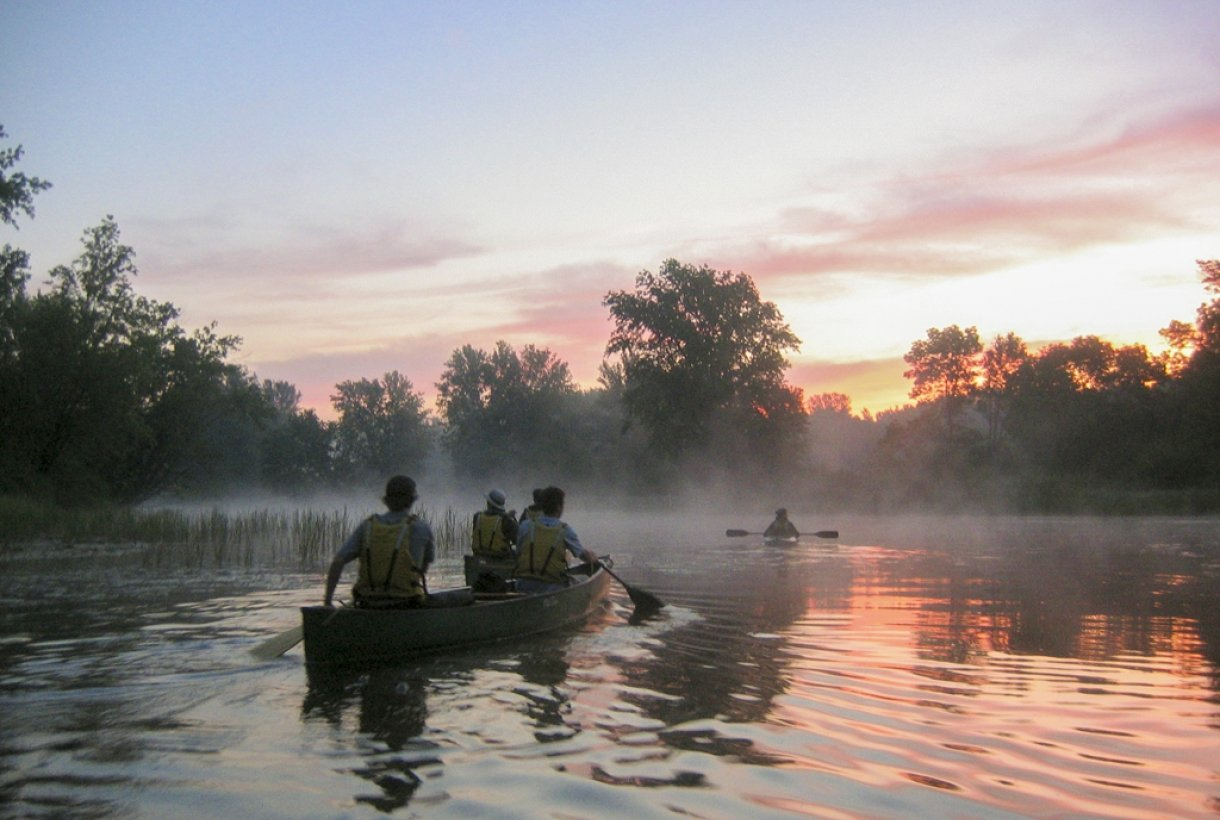 A kayak and 2 2-person canoes on the foggy Saint Croix National Scenic River at sunrise.