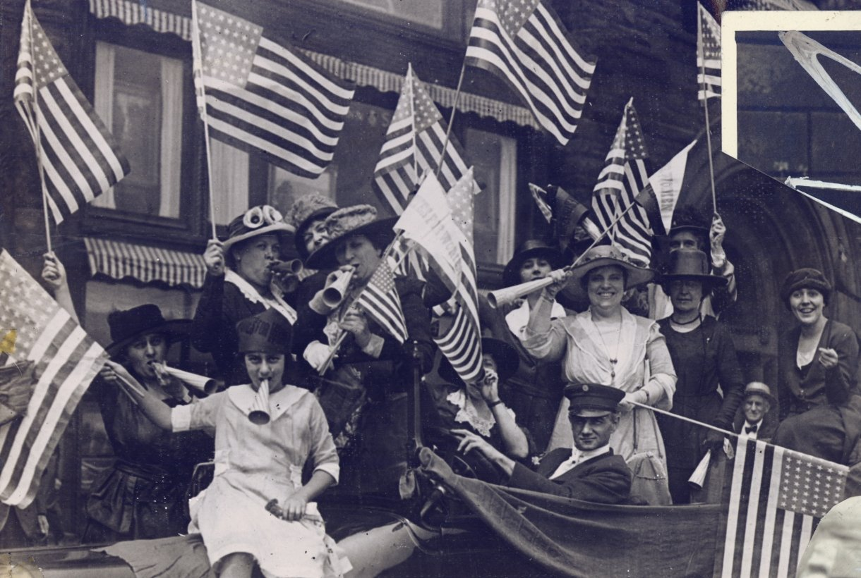 Women celebrating by waving flags and blowing horns. By Carrie Chapman Catt albums, Special Collections Department, Bryn Mawr College Library