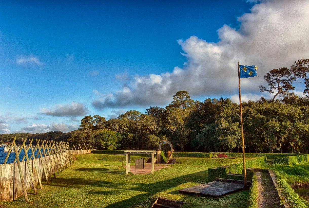 Blue flag with 3 yellow fleur-de-lys symbols waving at a minimalist grass-covered Fort Caroline