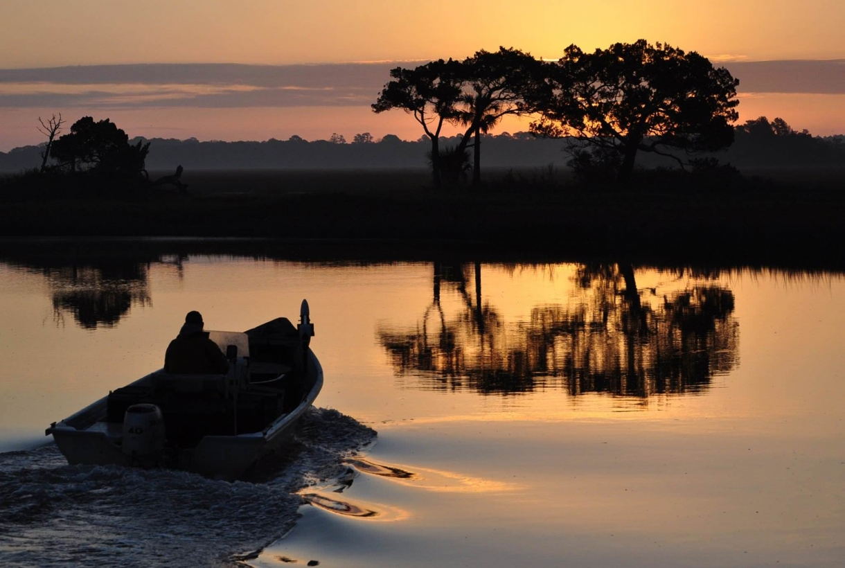A person on a boat at sunrise at Cedar Point boat ramp at Timucuan Ecological & Historic Preserve