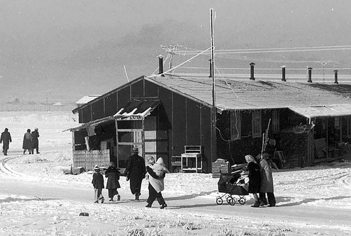 Black and white photo of people who were interned at Tule Lake during World War II. There is snow on the ground and people, bundled in winter clothes, walk next to a one-story wooden structure.