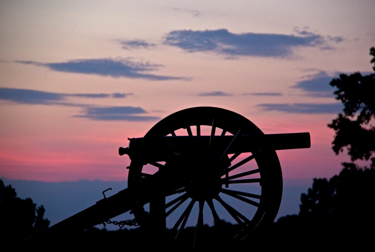A cannon is dark against a pink and purple sunset
