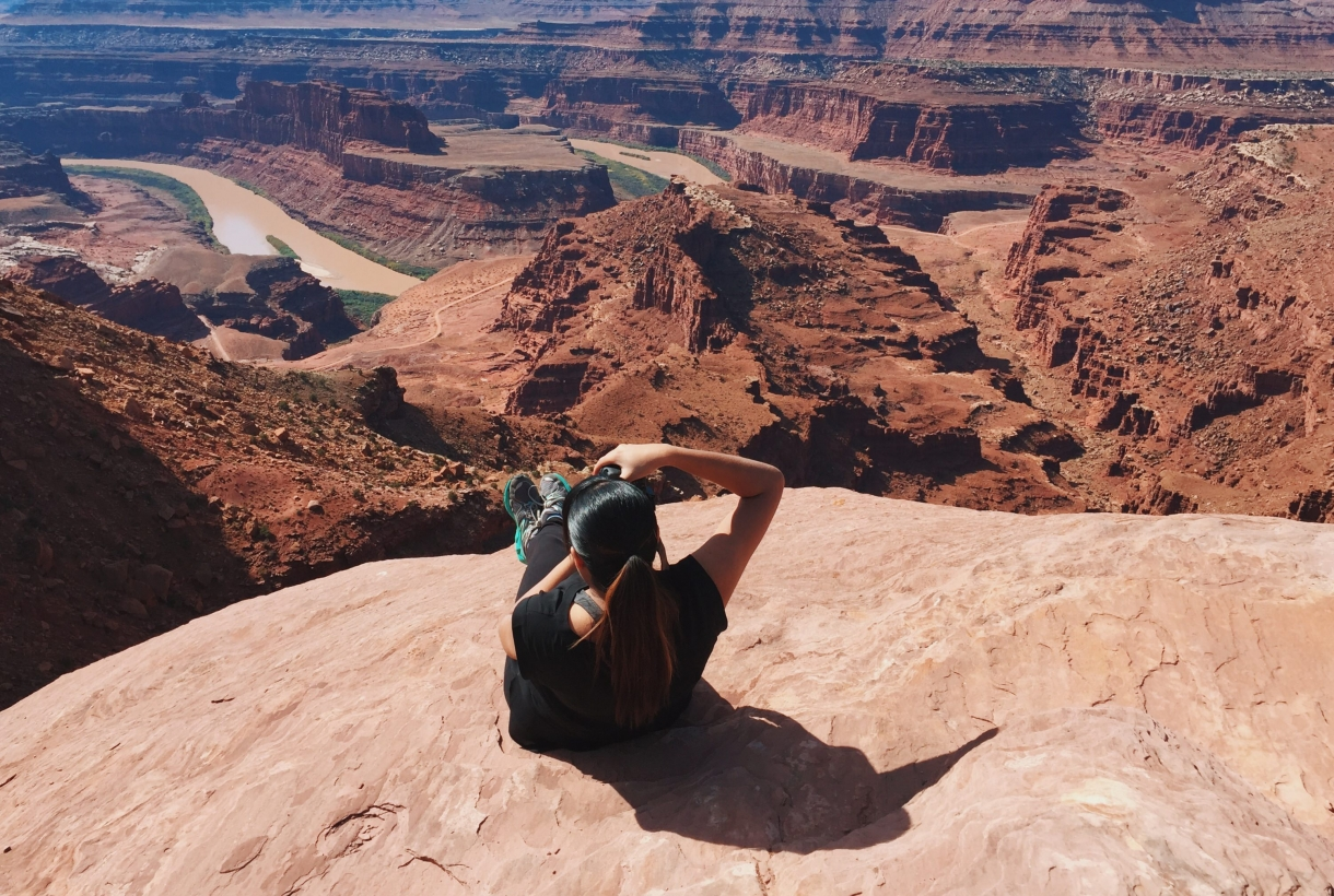Ambreen Tariq sitting on a rock taking a photo of the landscape in front of her at Canyonlands National Park