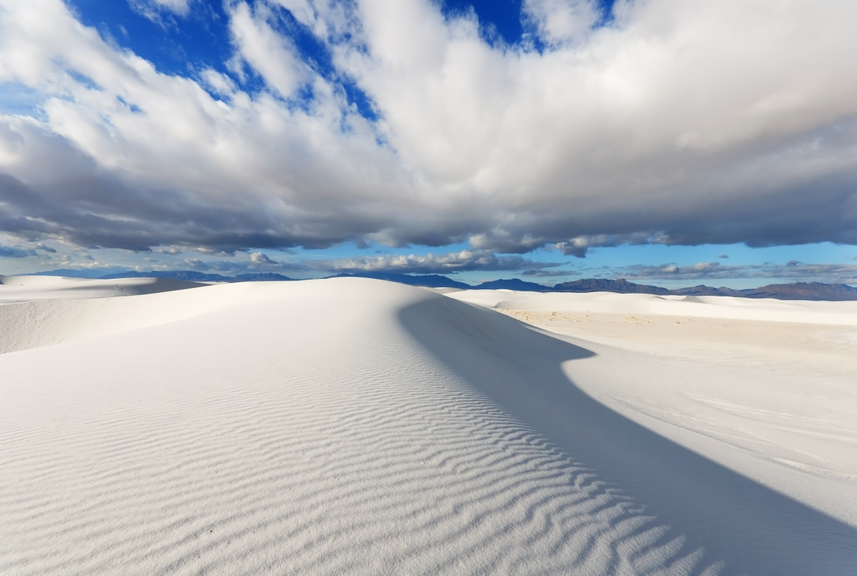 White Sands National Monument with a cloudy blue sky in the sun