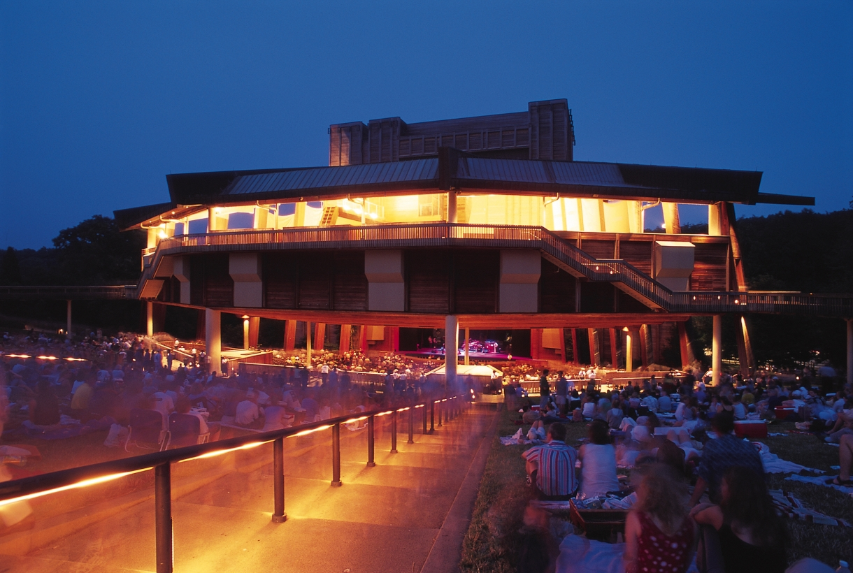 An illuminated wooden stage area with several patrons sitting in a grassy area around it