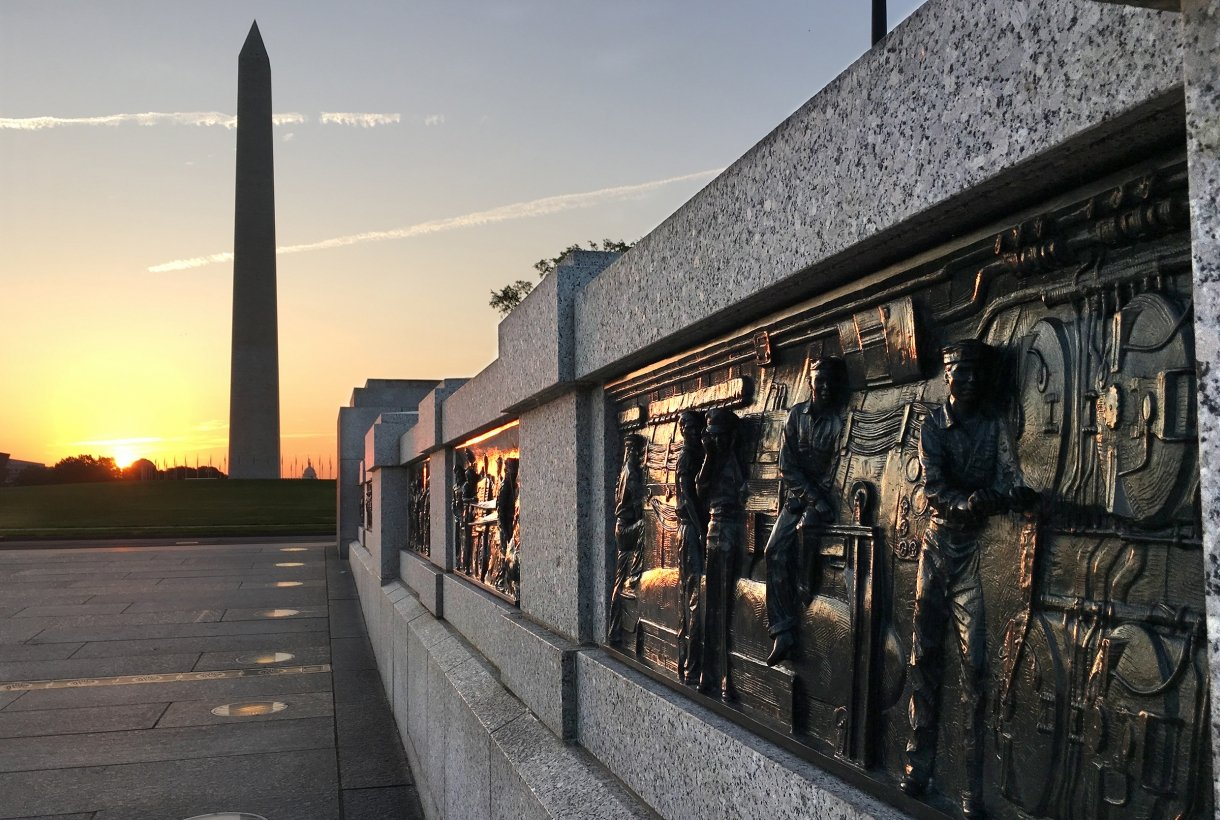 Dark, bronze, rectangular panels set into a light stone wall that stretches from the bottom right to the center of the photo, in the direction of the Washington Monument, a tall obelisk in the distance. The sun is on the horizon.