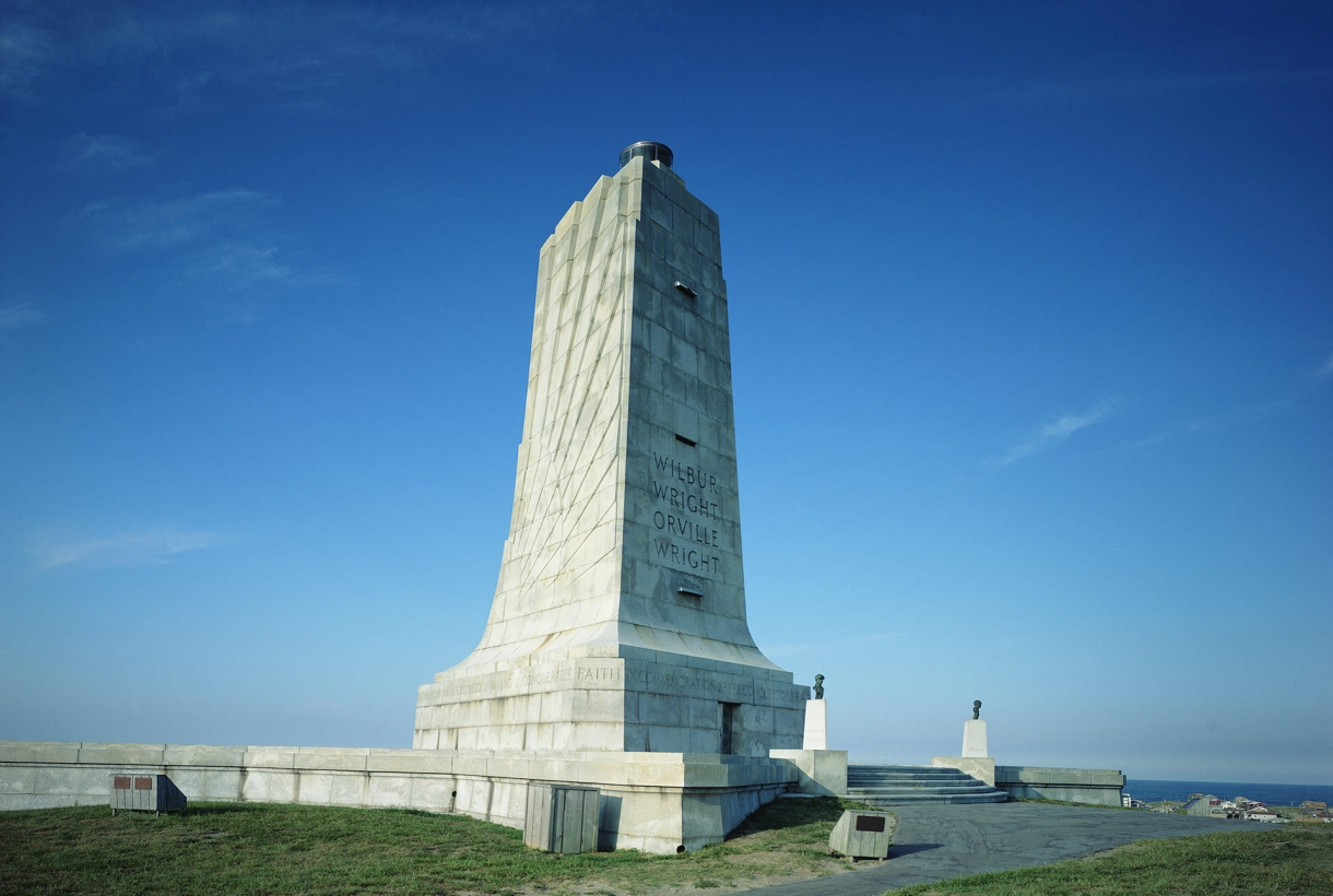 Image of granite-made Wilbur and Orville Wright Memorial with blue sky