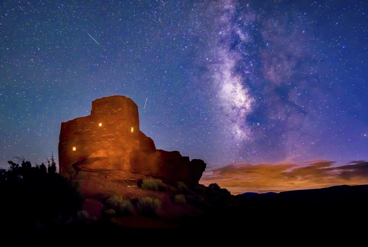 Glowing Wukoki Pueblo in Wupatki National Monument with the with the night sky and Milky Way in the background