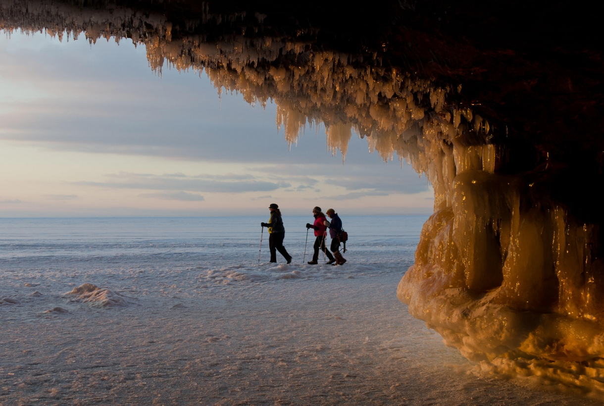 Three people trekking through the icy Apostle Islands National Lakeshore