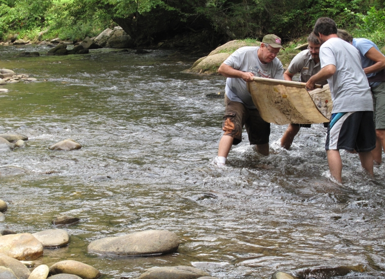A park ranger teaches people how to sift the river