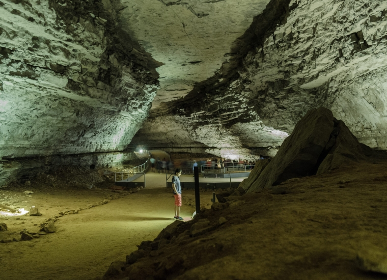 Visitor reading informational plaque inside Mammoth Caves