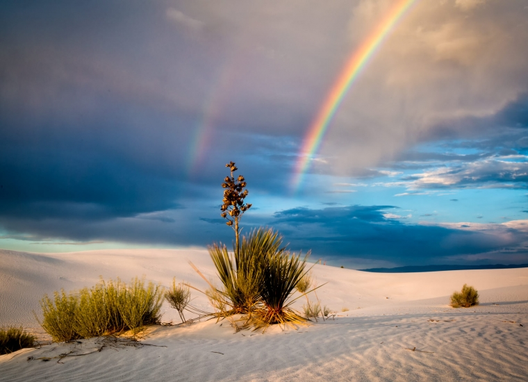 Double rainbow through rains on sunlit white sand dunes