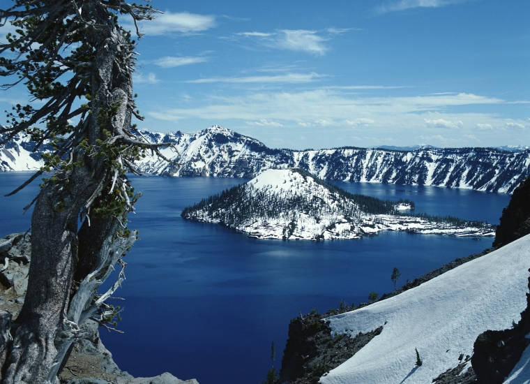 Crater lake and surrounding mountains covered in snow