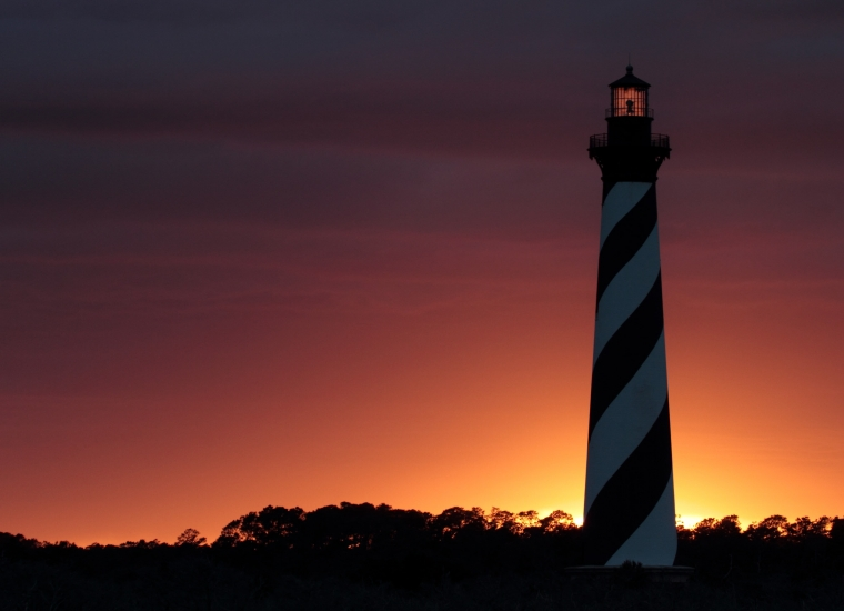Sun setting behind striped lighthouse tower Cape Hatteras National Seashore